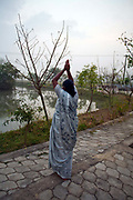 A resident makes a salutation to the sun at dawn before communal prayers at the Tamaraikulum Elders's Village