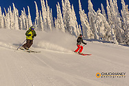 Skiers down the fresh groom on Hogans East at Whitefish Mountain Resort in Whitefish, Montana, USA model released