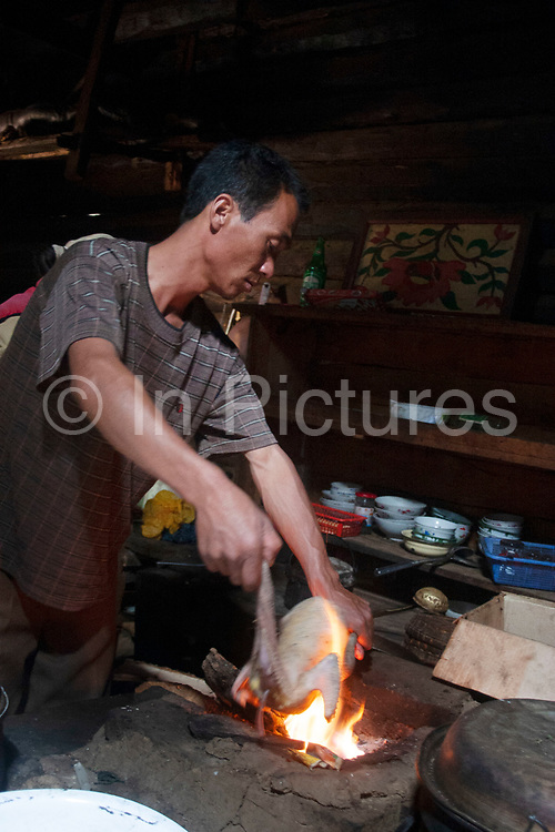 Mo Suo man prepares a chicken over the fire in a minority group in a small community village home near Lugu Lake, Yunnan, China. Leaders of such communities are women, who live mostly separate lives from the men of the village. They still lead very simple lives, tending their crops and animals. Local tradition is that if a man wished to be with any woman in the village, he must simply knock on her door at night. Should she become pregnant with his child, the man's brothers would have to raise the child.