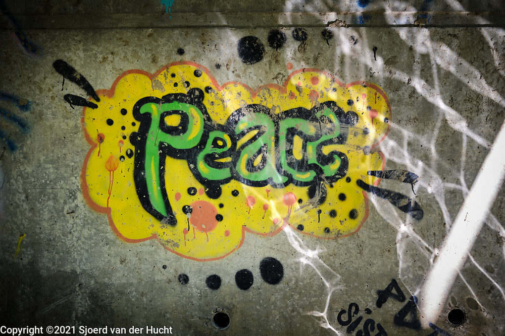 Drôme, Frankrijk - augustus 2021: Graffiti met tekst Peace op een muur onder een brug. | Drôme, France - August 2021: Graffiti with text Peace on a wall under a bridge.