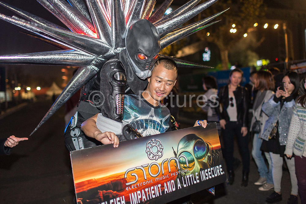 A sideshow actor dressed up an alien confronts a Chinese youth at the Storm Music Festival, a gathering of big names in electronic music  in Shanghai, China on 12 December 2013.