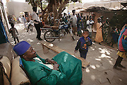 Soumana Natomo relaxes and watches scores of well-wishers dance in the narrow dirt lanes of his village of Kouakourou, Mali. They are on their way to the town hall to witness the official marriage license signing, which only his daughter Pai and her soon-to-be-husband sign.