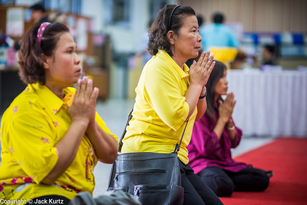 26 NOVEMBER 2012 - BANGKOK, THAILAND:  Women pray for the hospitalized King of Thailand at Siriraj Hospital in Bangkok. Siriraj was the first hospital in Thailand and was founded by King Chulalongkorn in 1888. It is named after the king's 18-month old son, Prince Siriraj Kakuttaphan, who had died from dysentery a year before the opening of the hospital. It's reported to one of the best hospitals in Thailand and has been home to Bhumibol Adulyadej, the King of Thailand, since 2009, when he was hospitalized to treat several ailments. Since his hospitalization tens of thousands of people have come to pay respects and offer get well wishes. The King's 85th birthday is on Dec 5 and crowds at the hospital are growing as his birthday approaches. The King is much revered throughout Thailand and is seen as unifying force in the politically fractured country.       PHOTO BY JACK KURTZ