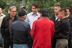 Prime Minister Justin Trudeau, back centre, listens to First Nations members along with Grand Chief Edward John, back left, during a visit to the Prince George Fire Centre, in Prince George, B.C., on Thursday August 23, 2018. Photo by Darryl Dyck/CP/ABACAPRESS.COM