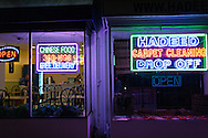 Night view of a carpet store and restaurant with bright neon signs. WATERMARKS WILL NOT APPEAR ON PRINTS OR LICENSED IMAGES.