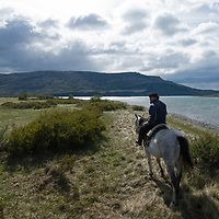 A Chilean gaucho rides by Lago de Toro in Torres del Paine National Park, Patagonia, Chile.