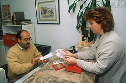 Woman changing money in a small bank,