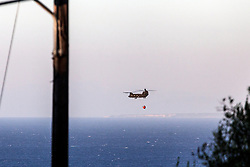 August 14, 2017 - Zakynthos, Greece - A military helicopter approaches the sea to fill water from the  eastern  part of Zakynthos (Zante) on August 14, 2017. Wildfires sweep the island of Zakynthos (Zante) during the past few days among declarations of officials for suspected arson. On August 14, the island was declared in state of emergency. (Credit Image: © Kostis Ntantamis/NurPhoto via ZUMA Press)
