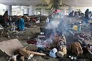 A homeless mother cooks breakfast  by the railway tracks where her family lives. Okhla, New Delhi, India