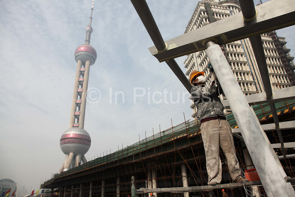 Workers on a construction site in Pudong Financial District with the Pearl Oriental Tower standing in the distance in Shanghai, China on 15 January 2010. Shanghai is on its way of becoming one of the world's most important financial centers.