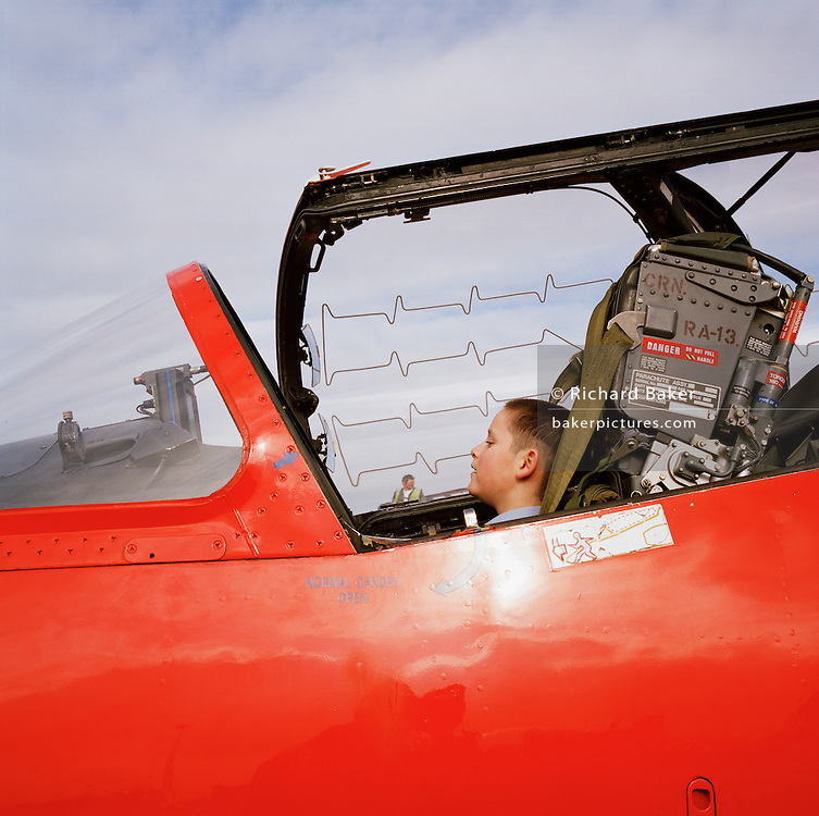 Younf air cadet sits in Hawk cockpit of the Red Arrows, Britain's RAF aerobatic team during visit to RAF Scampton.