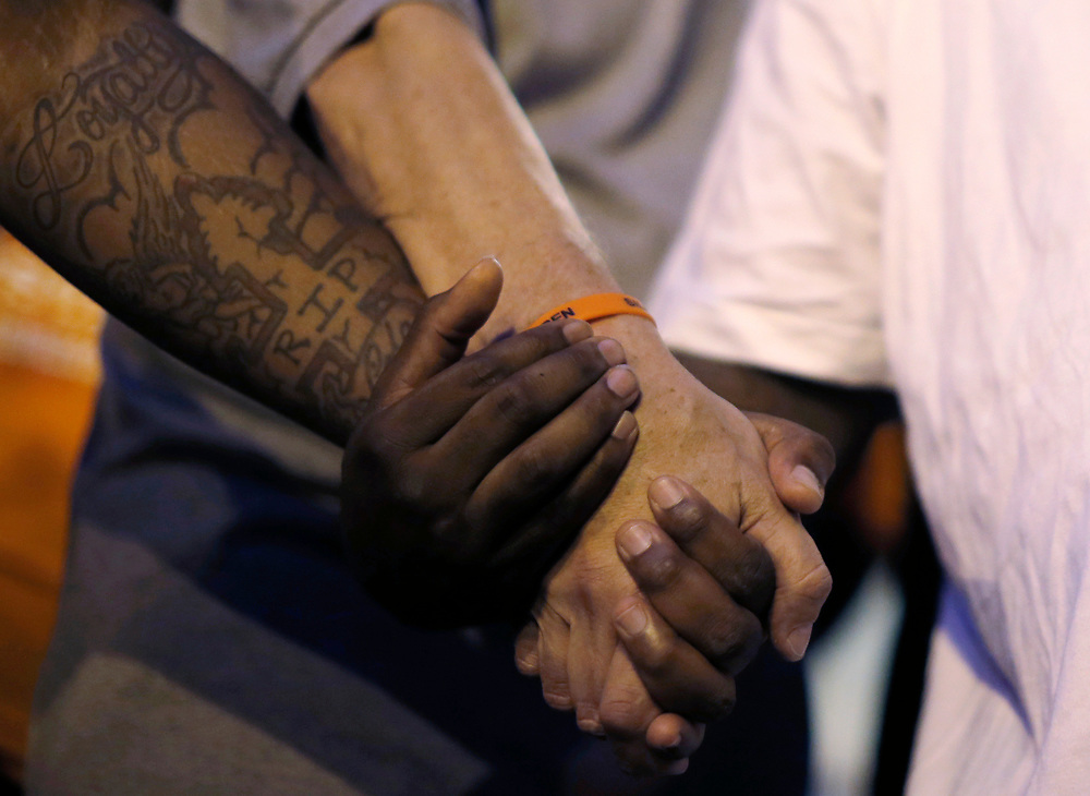 Father Michael Pfleger (C) holds hands in prayer with attendees at Saint Sabina Church before taking part in a weekly night-time peace march through the streets of a South Side neighborhood in Chicago, Illinois, September 16, 2016.  REUTERS/Jim Young