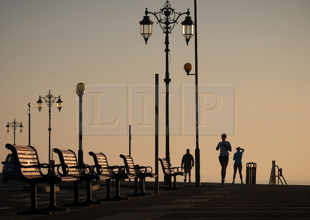 © Licensed to London News Pictures. 06/11/2017. Southsea, UK.  People enjoying the cold but clear morning along the promenade during sunrise in Southsea this morning, 6th November 2017. Photo credit: Rob Arnold/LNP