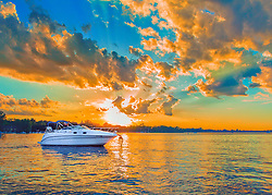A fiery sunset on Lake Minnetonka in Minnesota. The warm setting sun casts fiery light across the skies above the water warming the clouds and waters below