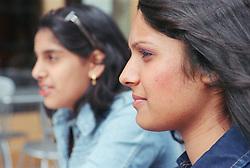 Two teenage girls looking thoughtful,