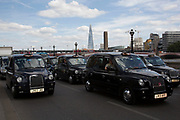 London, UK. Wednesday 11th June 2014. Black taxi drivers protest against taxi service app Uber, brings central London to a standstill on Victoria Embankment, with The Shard in the background. Joined in many numbers by future black cab drivers on mopeds currently doing 'The Knowledge'. London cabbies emphasised that they had no problem with Uber, only with Transport for London for not enforcing current legislation. Taxi drivers say the Uber app is tantamount to a meter and should be regulated like taxi meters. Uber says it has seen an 850% increase in sign-ups compared to last Wednesday and describes the London Taxi Drivers Association (LTDA), as being stuck in the dark ages.