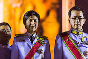 05 DECEMBER 2013 - BANGKOK, THAILAND:  YINGLUCK SHINAWATRA the Prime Minister of Thailand, and ANUSORN AMORNCHAT, her husband, (right) on stage the celebration of the birthday of the King in Bangkok. Thais observed the 86th birthday of Bhumibol Adulyadej, the King of Thailand, their revered King on Thursday. They held candlelight services throughout the country. The political protests that have gripped Bangkok were on hold for the day, although protestors did hold their own observances of the holiday. Thousands of people attended the government celebration of the day on Sanam Luang, the large public space next to the Grand Palace in Bangkok.    PHOTO BY JACK KURTZ