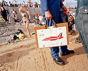 A member of the elite 'Red Arrows', Britain's prestigious Royal Air Force aerobatic team, sells Rolls-Royce-sponsored charity posters of their workhorse Hawk jet aircraft for £5 (?10) each on the beach at Clacton-on-Sea after the Air Show on West Greensward on the sea front. It is a hot summer's afternoon but wearing black heavy-duty RAF regulation boots and the distinctive, specially-tailored  blue overalls, is a member of the team's support ground-crew (known as the Blues). Their jobs might include engineering, operations or administration work. Secondary duties are asked of them too and here we see the lower body of photographer Senior Aircraftman (SAC) Matt Reid who holds a hardened folder containing the scaled artwork while standing on the soft sand. The crowd mingles in the background and a lady dressed in only a bikini returns to her possessions. .
