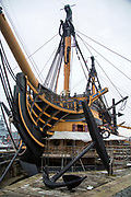 The British Royal Navy's most famous warship, HMS Victory now undergoing restoration as a living museum in Portsmouth Historic Dockyard, Hampshire, UK.  This battleship is most famous as Admiral Lord Nelson's flagship at the Battle of Trafalgar in 1805. The large anchor is on display.