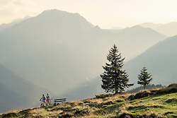 Couple of mountainbikers looking at view in alpine landscape, Zillertal, Tyrol, Austria