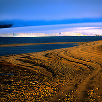 FRANZ JOSEF LAND, RUSSIA.  Shoreline of Bell Island & glacier on Mabel Island (bkg) in this Arctic Ocean archipeligo.