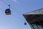 Emirates Air Line cable cars pass The Crystal Building in Royal Victoria Docks, London, England, United Kingdom.  The Air Line opened in 2012  and was built by Doppelmayr with sponsorship from the airline Emirates.  The Crystal Building is one of the worlds most sustainable buildings and events venue.  (photo by Andrew Aitchison / In pictures via Getty Images)