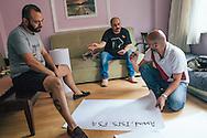 Salah (L), and Mr Gay Syria judges Samer (C) and Mahmoud (R) prepare banners for Istanbul Pride 2015, Taksim, Istanbul, Turkey.