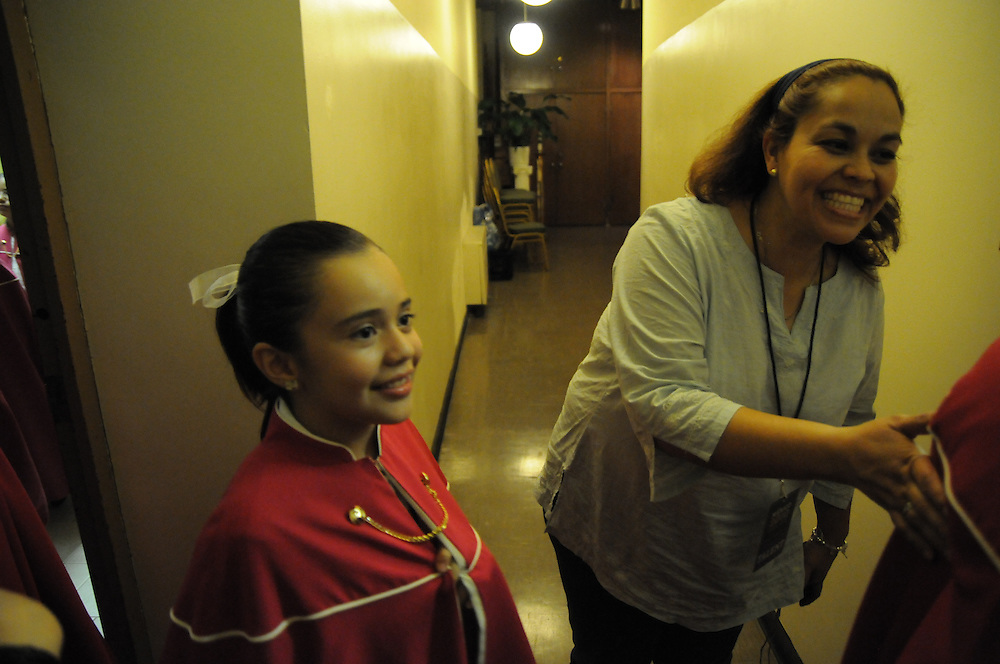 Choir parent Lorena Alcaraz makes a final quality control check backstage as Niños Cantores de Morelia of Michoacan, Mexico head for performance before a packed audience at St. Gall Parish on Chicago's southwest side.