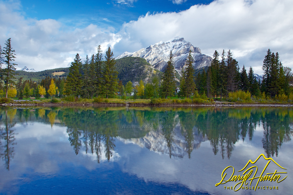 Cascade Mountain casts a reflection on the calm water of the Bow River as it flows through the town of Banff in Banff National Park.