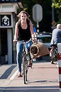 Een meisje fietst met een kattenmand door Utrecht.<br /> <br /> A girl is cycling with a basket for a cat.