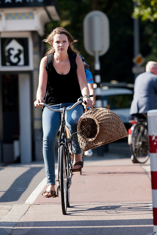 Een meisje fietst met een kattenmand door Utrecht.<br /> <br /> A girl is cycling with a basket for a cat.