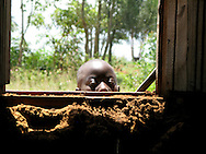 A Rwandan boy peeks through an open window to check out what is going on inside a church near Kigali in the middle of a weekday.