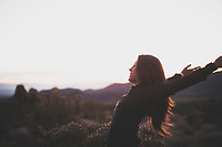 Athletic woman with arms wide open in the desert before sunrise.