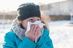 Close-up of girl blowing nose in winter