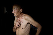 77 year old Lu Zhitian stands in front of his house in a rural village near Fuyang, Anhui Province,  China on 28 August  2013.  As able-bodied adults seek work in cities in hopes of better income, more and more villages in China are inhabited mostly by the elderly and children.