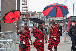 © licensed to London News Pictures. London, UK 01/01/2000. Lloyd Benson, Abrajah Rafiq and Isaac Stephen walking with umbrellas under the rain after handing out tea gift packages from Kenya to London commuters to celebrate Queen?s Diamond Jubilee this morning on London Bridge. Photo credit: Tolga Akmen/LNP