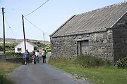 Family walking along small country road, Inishmore, County Clare, Ireland