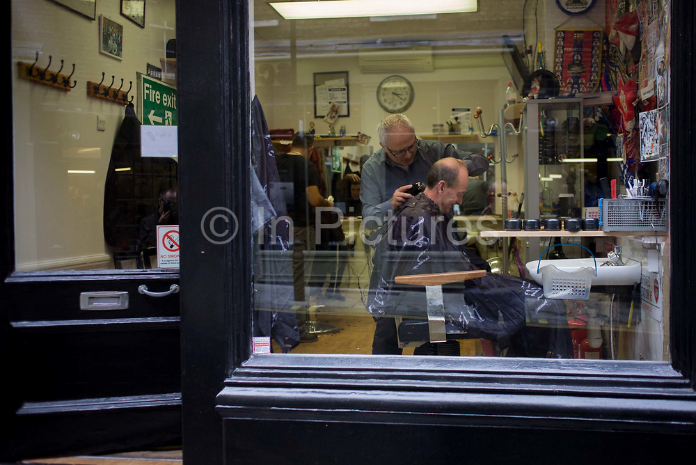 A gentleman has his neck clippered in a barber shop in central London. Seen through the glass of this small business located in a narrow lane in the capital's West End. The customer smiles as they chat during the haircut, the banter is friendly and relaxed. In the background there is shop clutter with footballs banners on the wall and a sink for washing and shampooing.