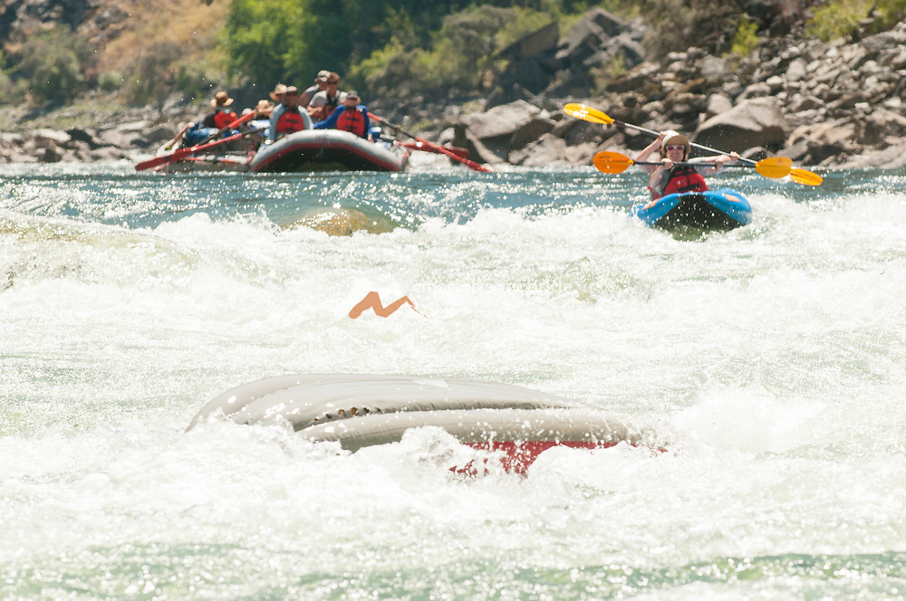 Inflatable kayak flipping in Weber rapid in the Impassible Canyon on the Middle Fork of the Salmon River during six day rafting vacation, Idaho.