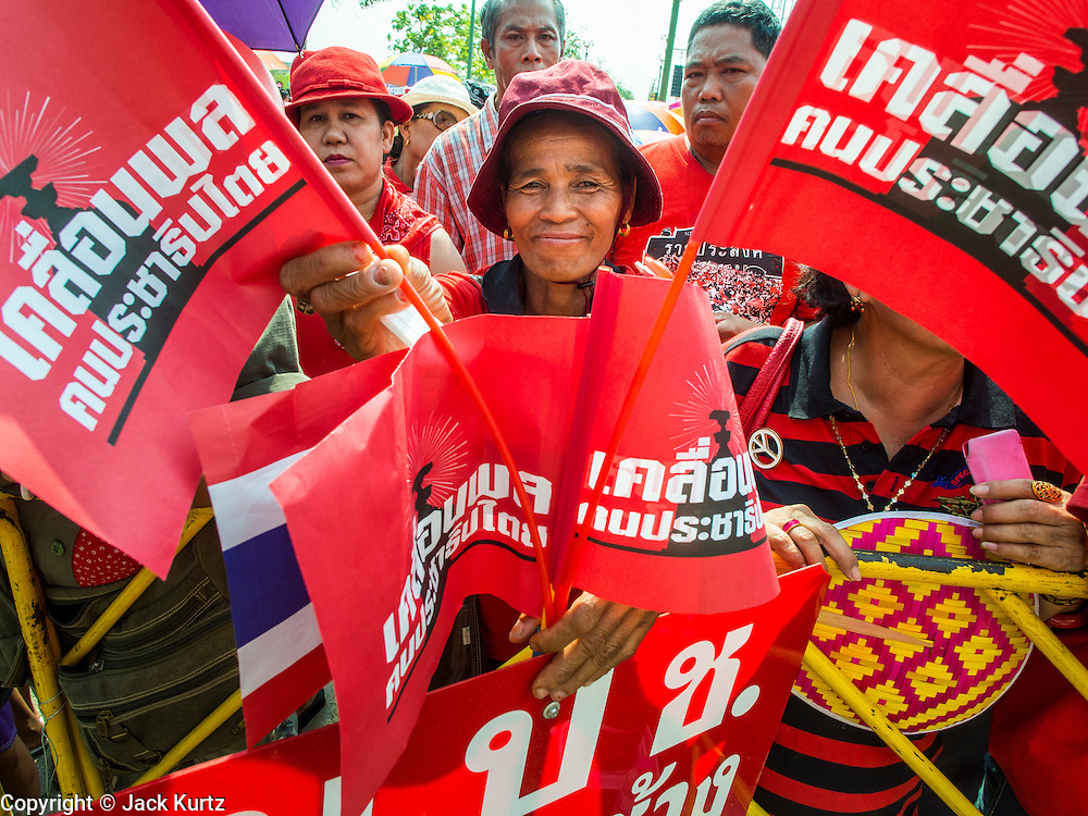 06 APRIL 2014 - BANGKOK, THAILAND:  A Red Shirt supporter framed by Red Shirt flags at a Red Shirt rally in the Bangkok suburbs Sunday. Red Shirts and supporters of the government of Yingluck Shinawatra, the Prime Minister of Thailand, gathered in a suburb of Bangkok this weekend to show support for the government. The Thai government is dealing with ongoing protests led by anti-government activists. Legal challenges filed by critics of the government could bring the government down as soon as the end of April. The Red Shirt rally this weekend was to show support for the government, which public opinion polls show still has the support of most of the electorate.  PHOTO BY JACK KURTZ