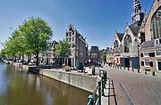 Nederland, Amsterdam, 7-5-2020 De regering laat het normale dagelijks leven weer langzaam opstarten . Door de afwezigheid van toeristen is het ongewoon rustig in de binnenstad van Amsterdam en is de stad te zien zoals die pakweg voor de eeuwwisseling was . Zicht op de Oudezijds voorburgwal, Oude Kerk op de wallen, red light district . . typisch,amsterdams,iconisch,historische,bebouwing,architectuur . Unlock,beperkende,beperkingen, opheffen,versoepelen,versoepeling , opengooien, massatoerisme,toeristisch, toeristische, toerisme, Foto: Flip Franssen