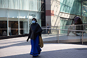 Woman wearing a surgical face mask near the iconic Bully Bullring statue on 24th April 2020 in Birmingham, England, United Kingdom. Coronavirus or Covid-19 is a new respiratory illness that has not previously been seen in humans. While much or Europe has been placed into lockdown, the UK government has extended stringent rules as part of their long term strategy, and in particular social distancing.
