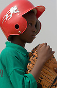 A Ghanaian boy wearing a baseball helmet holds his glove as he waits for the game to start in Tema, roughly 35 km east of Ghana's capital Accra on Saturday February 3, 2007. The exhibition game was being held on the occasion of the visit of a delegation from the American Major League Baseball Association made possible by the African Development Foundation, a non-profit organization that supports little league projects in selected African countries.
