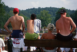 Shirtless backs of four guys watching a race