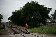 """Irma, an asylum-seeker from Honduras, crosses train tracks on her walk home from work in Forth Worth, Texas, U.S., May 10, 2019. Irma's husband, Jose, was murdered back home. Still grieving for her husband, she has struggled to adjust to American life. Every time something new happens, she said, """"I want to tell him about it."""" She has arrived with straightforward expectations. """"I thought the children would go to school, and I'd work, and I'd get settled,"""" she said. """"But it's been very difficult here."""""""