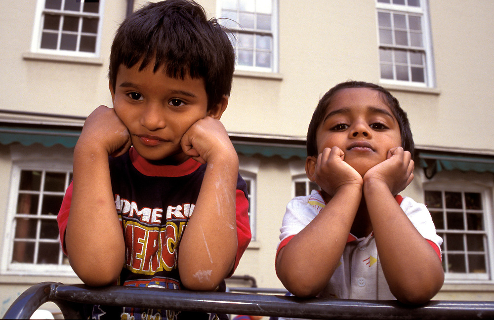 two children leaning on their elbows at nursery school,