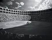 Light shines into a bullfighting stadium in Madrid, Spain creating a shadow across half of the inner field