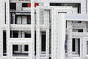Detail of PVC double-glazing window frames outside a glazier shop in a south London street. Geometric shapes and mathematical sums can be seen here in this detail of the new products leaning against the wall of the business in Brockley in the borough of Lewisham. The white surfaces are partially covered with protective tape, keeping them clean and fresh before being fitted on a home nearby.