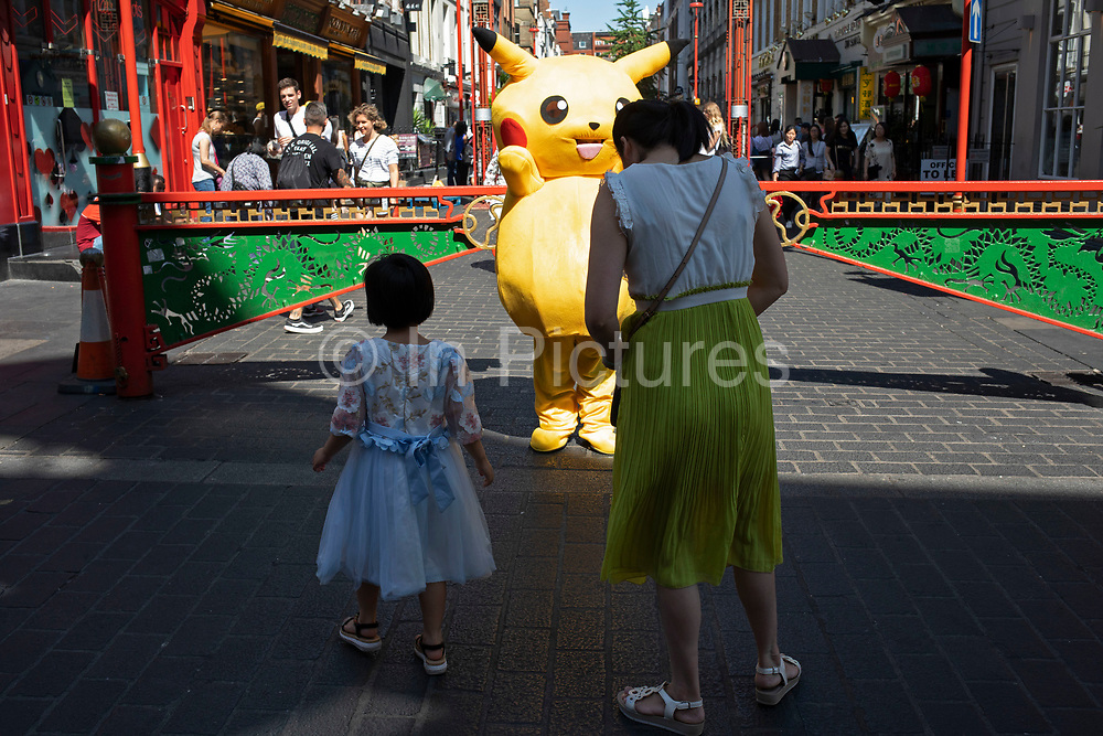Pokemon Pikatchu who people pay to have their picture taken with in Chinatown, London, England, United Kingdom. Pikachu are a species of Pokemon, fictional creatures that appear in an assortment of video games, animated television shows and movies, trading card games, and comic books licensed by The Pokémon Company, a Japanese corporation.