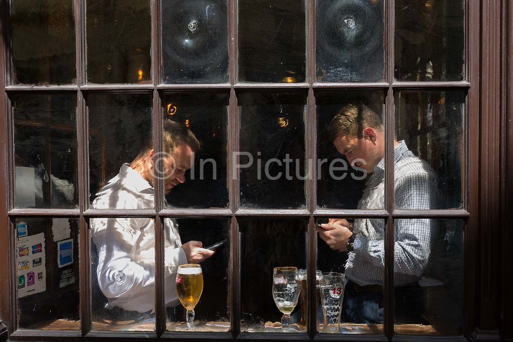 Two businessmen look at their phones in the window of a pub in Lime Street in the heart of the capitals financial district, on 26th June, in the City of London, England.